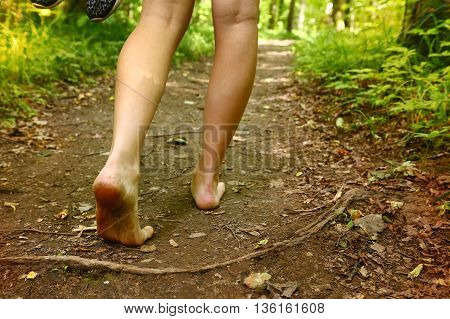 long legs with bare feet walking along the forest path with trainer shoes holding hands close up photo