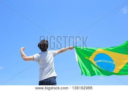 Back view of a excited man holding a brazil flag with blue sky