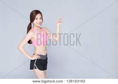 Sport girl pointing something isolated on gray background. Running fitness sport woman smiling happy. asian beauty