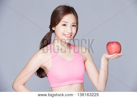 Sport girl with an apple on her hand isolated on gray background. Running fitness sport woman smiling happy. asian beauty