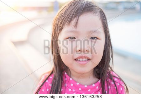 Happy Cute little girl on the meadow in summer day asian