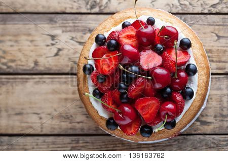 Fresh strawberry cake homemade traditional gourmet sweet dessert bakery food decorated with berries and whipped cream on rustic background table
