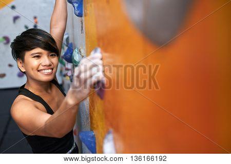 Portrait of lovely young Vietnamese girl enjoying climbing