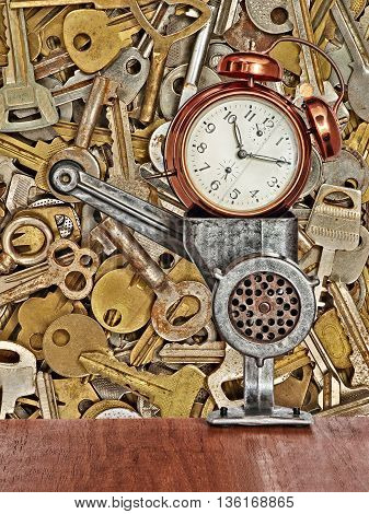 Retro alarm clock in meat grinder on old metal keys background taken closeup.