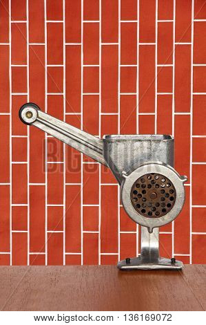 Old manual meat grinder on red brick wall background taken closeup.