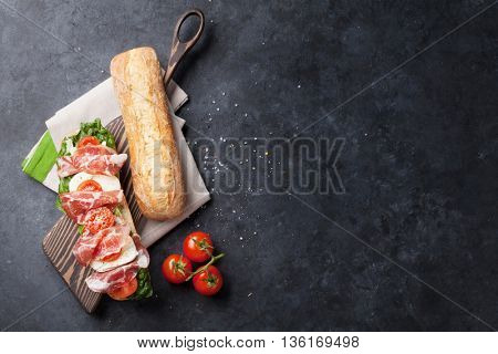 Ciabatta sandwich with romaine salad, prosciutto and mozzarella cheese over stone background. Top view with copy space