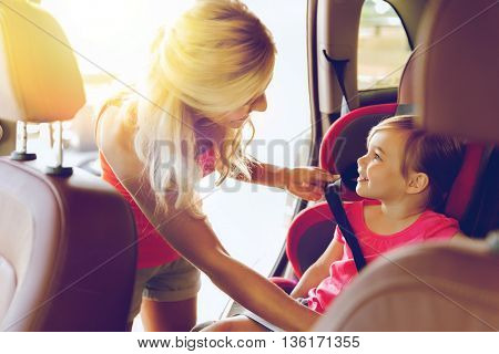family, transport, safety, road trip and people concept - happy mother fastening child with car seat belt poster