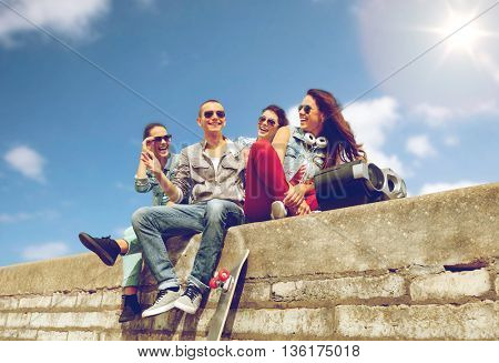 summer holidays and teenage concept - group of smiling teenagers with boob box and skatboard hanging out outside