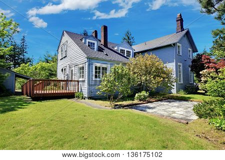 Classic House With Curb Appeal. View Of Wooden Walkout Deck And Grassy Filled Garden