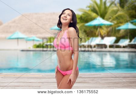 people, travel, tourism, swimwear and summer holidays concept - happy young woman in pink bikini swimsuit over swimming pool and sunbeds at exotic hotel resort background