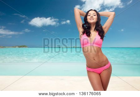 people, travel, tourism, swimwear and summer holidays concept - happy young woman posing in pink bikini swimsuit with raised hands over exotic tropical beach background