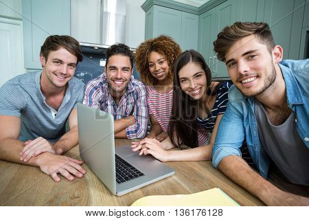 Portrait of young friends smiling while using laptop on table at home