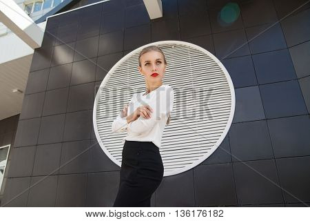 Beautiful blonde businesswoman with red lips looking away against of building wall