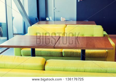 design, public place, furniture and interior concept - close up of restaurant interior with table and sofas