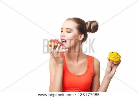 Portrait of young brunette with buns eating donuts.Studio shot