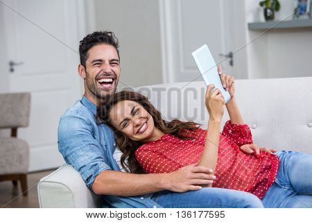 Portrait of cheerful couple with digital tablet at home