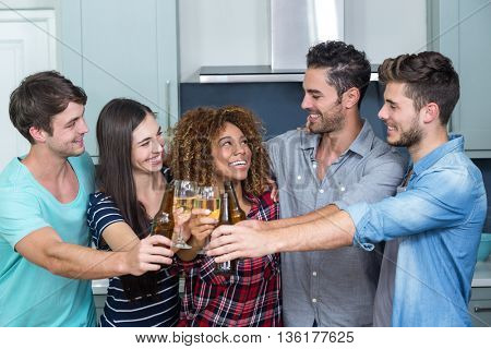 Cheerful multi-ethnic friends toasting beer and wine in kitchen at home