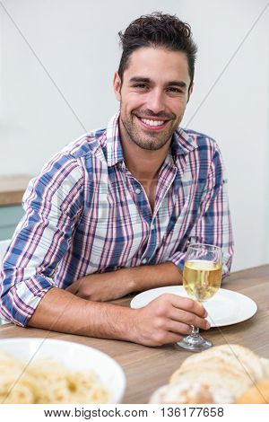 Portrait of handsome young man drinking wine at table in house