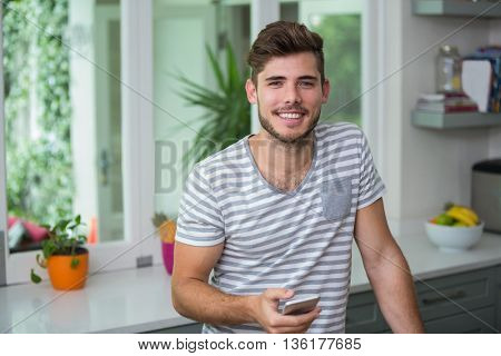 Portrait of smiling man holding phone at home