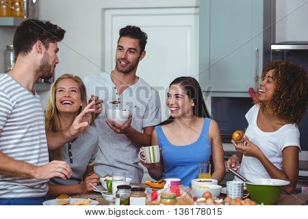 Cheerful friends discussing while having breakfast at table in kitchen
