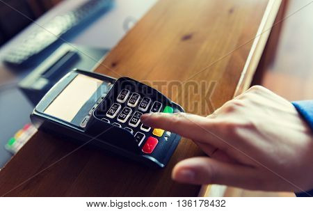 finance, technology, payment and people concept - close up of hand entering pin code to money terminal
