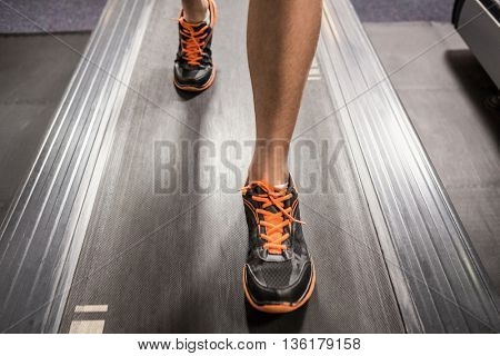 Close-up of man's feet while walking on thread mill at gym