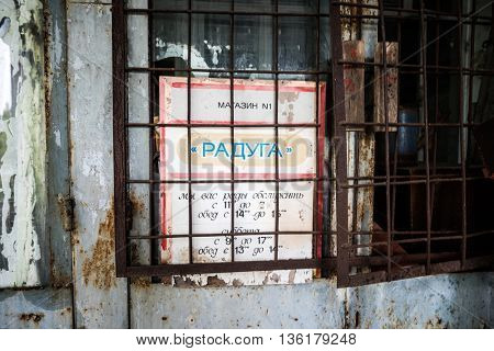 Pripyat, Ukraine - May 29, 2016: store window with sign board behind rusty grating in Pripyat, Chernobyl, Ukraine