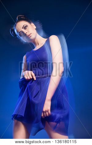 Portrait of beautiful young model posing in blue dress against of blue background.Long exposure