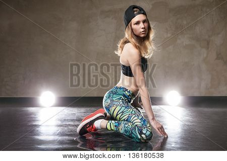 Portrait of stylish street dancer looking at camera.Studio shot.Illumination.