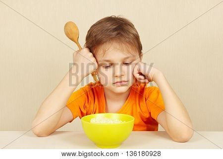Little unhappy boy does not want to eat a cereal