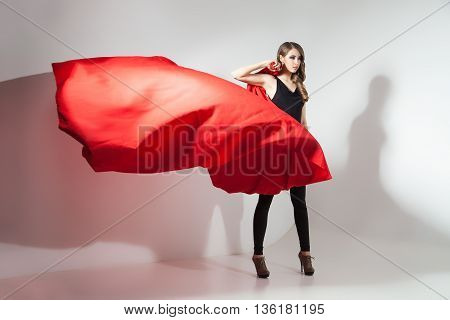 Side view of young model holding waving red cloth on white background