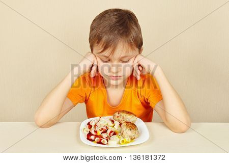Little boy does not want to eat a pasta with cutlet