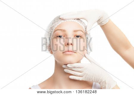 Portrait of young woman in medical hat looking at camera while doctor touches her face.Isolated