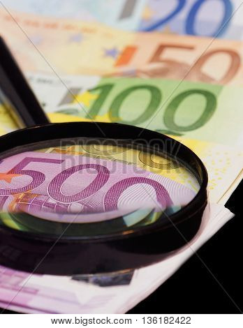 Euro banknotes are under a large magnifying glass