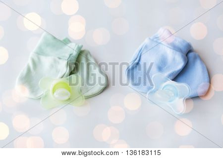 clothing, babyhood, accessory and object concept - close up of baby mittens and soothers for newborn twins