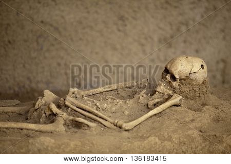 Human skeleton with trepanned skull lying in the grave