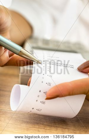 Closeup of female accountant working by checking a printout or receipt coming out of adding machine looking at numbers holding a pen.