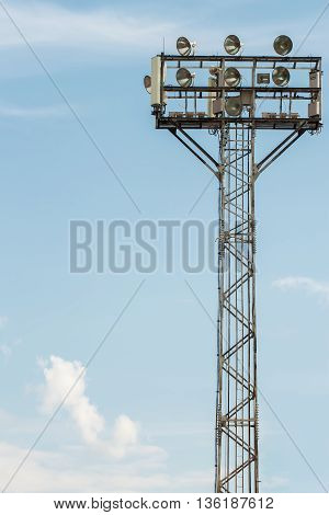 Large tall high outdoor stadium spotlights on rigid frame construction with blue sky background
