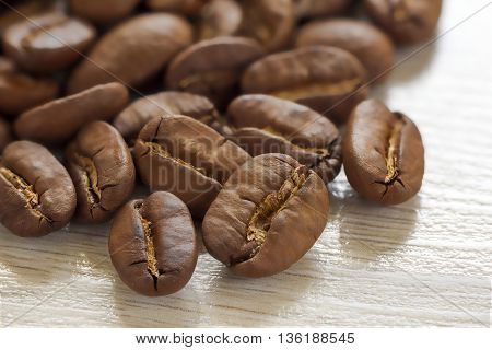 Broun coffee beans isolated on textured wooden background with shallow depth of field