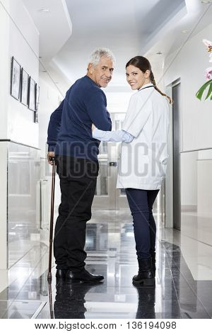 Rear View Of Female Doctor Walking With Senior Patient