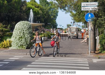Rimini, Italy - Circa August 2013: Twins girls on bikes crossing the street near Federico Fellini park.