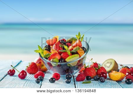 Fresh fruit salad placed on wooden planks, blur sea on background. Concept of healthy eating, antioxidants and summer time.