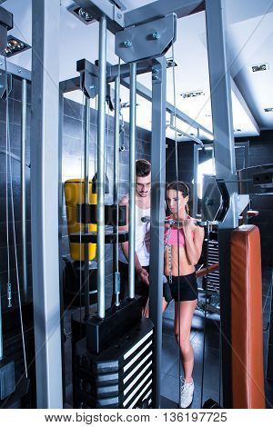 A young woman with her personal trainer working out in the Gym.