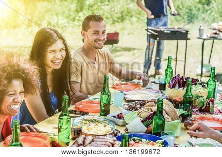 Group of young people enjoying park outdoor barbecue - Multi ethnic cheerful friends eating and drinking together - Summer meal and party concept - Soft focus on white girl - Warm desaturated filter