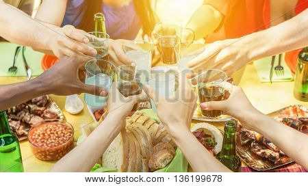 Group of friends toasting with aperitif eating barbecue outdoor - Closeup of hands cheering with cocktails and beers - Friendship summer fun and dinner concept - Soft focus on right bottom hand