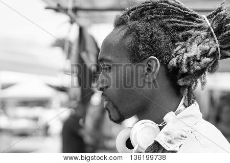 Portrait of thoughtful black man outdoor in a weekly clothhes market - Young rasta guy with headphones in New York - Love sadness concept - Black and white editing - Soft focus on face - Warm filter