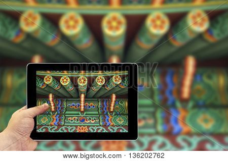 Tablet photography concept. Taking pictures on a tablet. Green Chinese ethnic painted wooden blockhouse poster