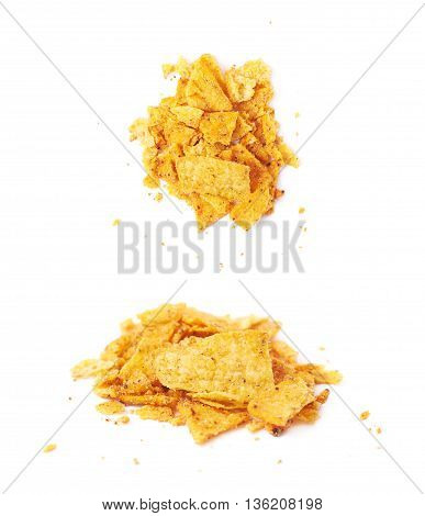 Pile of broken tortilla corn chips crumbles isolated over the white background, set of two different foreshortenings