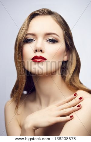 Gorgeous young blond woman with red lips and nails. Shallow depth of field