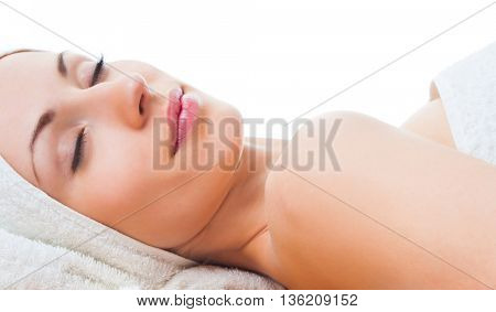 beautiful woman with closed eyes lying on table in spa
